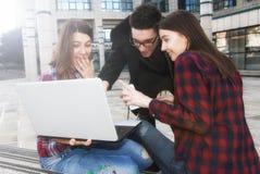 Tres estudiantes sonrientes felices del adolescente de la High School secundaria con el ordenador portátil a Imagenes de archivo