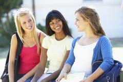 Tres estudiantes universitarios de sexo femenino que se sientan en banco con los libros de texto Imagenes de archivo