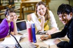 Tres estudiantes universitarios que estudian junto Foto de archivo libre de regalías