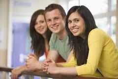 Tres estudiantes universitarios que se inclinan en la barandilla Fotografía de archivo libre de regalías