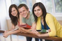 Tres estudiantes universitarios que se inclinan en la barandilla Imagen de archivo