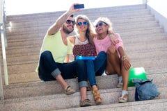Tres estudiantes universitarios que toman un selfie en la calle Imagen de archivo