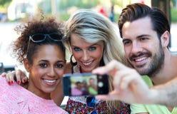 Tres estudiantes universitarios que toman un selfie en la calle Imagenes de archivo