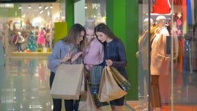 Tres excitaron a mujeres jovenes hermosas con los panieres en una tienda