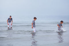 Tres felices, feliz, hermano juega en el mar Fotos de archivo