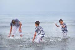 Tres felices, feliz, hermano juega en el mar Fotografía de archivo libre de regalías