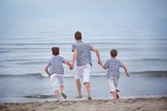 Tres felices, feliz, hermano juega en el mar Fotos de archivo libres de regalías
