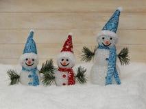 Tres felices muñecos de nieve en nieve mullida Fotos de archivo libres de regalías