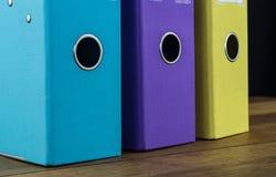 Tres ficheros coloridos del arco de la palanca en un escritorio Foto de archivo libre de regalías