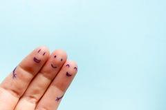 Tres fingeres sonrientes que son muy felices de ser amigos Concepto del trabajo en equipo de la amistad en fondo azul con el espa Imágenes de archivo libres de regalías