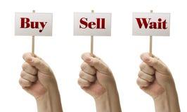 Tres firma adentro los puños que dicen la compra, la venta y la espera Imagen de archivo libre de regalías