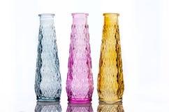 Tres floreros de vidrio coloreado con un modelo foto de archivo libre de regalías