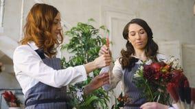 Tres floristas hermosos jovenes del cocinero trabajan en las flores dan fruto tienda que hace el ramo de la fruta y verdura