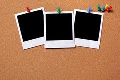 Tres fotos en blanco fijadas a un tablero del corcho Fotos de archivo