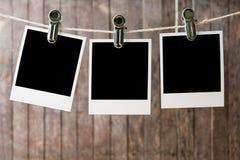 Tres fotos inmediatas en blanco que cuelgan en la cuerda para tender la ropa foto de archivo libre de regalías