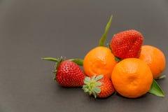 ¡Tres fresas y mandarines mandarín, mandarinas! Fruta cítrica muy dulce y sabrosa Fotos de archivo