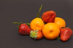¡Tres fresas y mandarines mandarín, mandarinas! Fruta cítrica muy dulce y sabrosa Fotografía de archivo libre de regalías