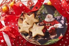 Tres galletas bajo la forma de estrella en la placa decorativa rodeada por las decoraciones de la Navidad Imagen de archivo libre de regalías