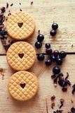 Tres galletas con un corazón con las bayas de la grosella negra fotos de archivo
