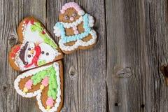 Tres galletas del pan de jengibre de la Navidad en la tabla de madera en la tabla de madera Fotografía de archivo libre de regalías