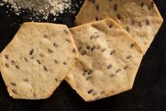 Tres galletas orgánicas y harina del grano entero en el negro Imagenes de archivo