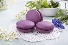 Tres galletas y flores púrpuras de los macarrones fotografía de archivo