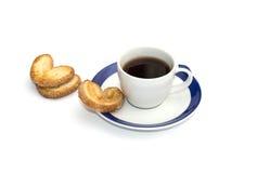 Tres galletas y tazas de café en un platillo con una frontera azul Fotos de archivo libres de regalías