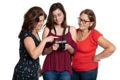 Tres generaciones de mujeres hisp?nicas que miran photpgraphs en una c?mara digital fotografía de archivo