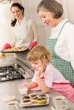 Tres generaciones de mujeres que cuecen al horno en cocina Foto de archivo libre de regalías