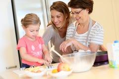 Tres generaciones que cuecen las galletas juntas Fotos de archivo libres de regalías