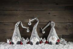 Tres gimps hechos a mano en el fondo de madera para el decorati de la Navidad Imágenes de archivo libres de regalías