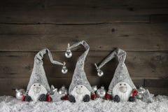 Tres gimps hechos a mano en el fondo de madera para el decorati de la Navidad Imagen de archivo