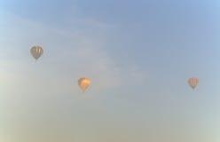 Tres globos del aire caliente en la niebla de la mañana Imágenes de archivo libres de regalías
