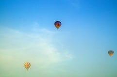 Tres globos del aire caliente que vuelan sobre la niebla de la mañana Fotos de archivo libres de regalías