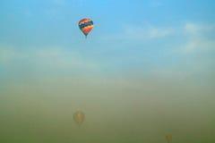 Tres globos del aire caliente que vuelan a través de la niebla de la mañana Imagen de archivo libre de regalías