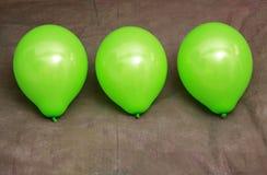Tres globos verdes contra el papel pintado marrón Foto de archivo libre de regalías