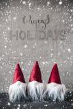 Tres gnomos rojos, cemento, copos de nieve, caligrafía buenas fiestas fotos de archivo libres de regalías