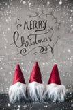 Tres gnomos rojos, cemento, copos de nieve, Feliz Navidad de la caligrafía fotos de archivo libres de regalías