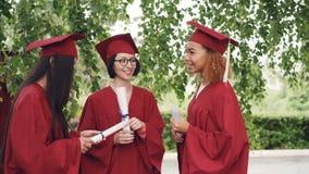 Tres graduados bonitos de las muchachas son que hablan y sosteniendo los diplomas el día de graduación, los estudiantes son orgul almacen de metraje de vídeo