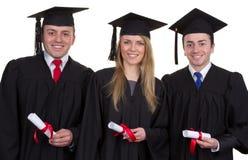 Tres graduados con las volutas que sonríen y aislados en blanco Imágenes de archivo libres de regalías