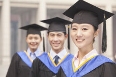 Tres graduados de la universidad que llevan los vestidos de la graduación y birretes que sonríen en fila Foto de archivo