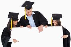 Tres graduados que señalan a la muestra en blanco foto de archivo libre de regalías