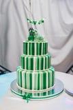 Tres grandes hermosos nivelaron el pastel de bodas adornado con dos pájaros en el top Un pastel de bodas rayado verde-blanco con Fotografía de archivo