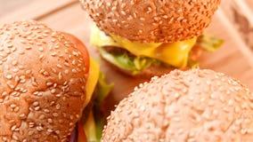 Tres hamburguesas apetitosas frescas con una ensalada y un tomate primer almacen de metraje de vídeo