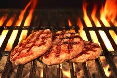 Tres hamburguesas bronceadas hechas en casa en la parrilla llameante caliente del Bbq Fotos de archivo libres de regalías