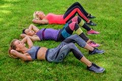 Tres hembras deportivas que hacen entrenamientos del ABS foto de archivo