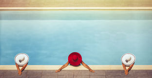 Tres hembras jovenes en sombreros en la piscina Fotografía de archivo libre de regalías