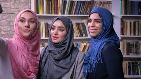Tres hembras musulmanes del hijab están tomando bastante imágenes y el selfie con el teléfono mientras que se colocan interiores, metrajes
