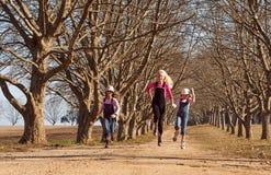 Tres hermanas de las muchachas que corrían saltar abajo de árbol alinearon el camino de tierra Imagen de archivo libre de regalías