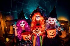 Tres hermanas divertidas lindas celebran el día de fiesta Los niños alegres en carnaval visten listo para Halloween imagen de archivo libre de regalías